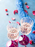 Two stemmed glasses with champagne on blue Royalty Free Stock Image