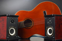 Two stereo audio speakers and classical acoustic guitar Stock Photography