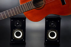 Two stereo audio speakers, and classical acoustic guitar Stock Photography
