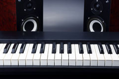Two stereo audio speakers and piano keys closeup on dark backgro Stock Image
