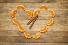 Two stick cinnamon and heart symbol made of  mandarin Stock Photography