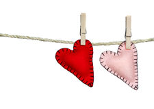 Two stitched hearts on a clothes line. Two stiched valentine hearts pink and red on a clothes line. They are handmade out of felt. Isolated on a white background Royalty Free Stock Photos