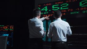 Two stock brokers in front of live market feed. Two stock brokers in front of a live global market feed in a bustling, futuristic office Stock Photo