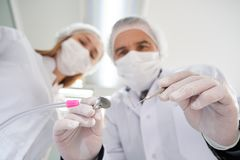 Two stomatologists looking at patient during examination. royalty free stock photography