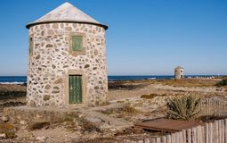 Two stone abandoned lighthouses on atlantic ocean coast. Medieval european architecture. Ancient navigation concept. Round lighthouses on Camino de Santiago stock photography