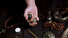Two stone balls in male hands and other Tibetan instruments