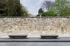 Two stone benches on the sidewalk of a city street. Two stone benches on the sidewalk of a street in a city next to a park stock images