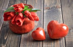 Two stone hearts and bunch of red tulips on wooden background Royalty Free Stock Images