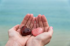 Two stone hearts on woman`s hands. Against blue ocean Stock Images