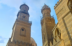 Two stone minarets. CAIRO, EGYPT - OCTOBER 10, 2014: Two neighboring minarets on Al-Muizz street compete in beauty and complexity of the carved decor, on October Stock Photos