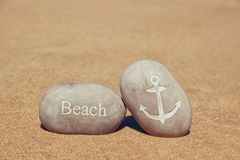 Two stone pebbles with the word beach and anchor sign over sandy beach Stock Photos