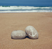 Two stone pebbles with the word beach and anchor sign over sandy beach and sea horizon Stock Photography