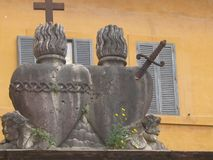 Two stone statues of hearts in front of a yellow building in the district Trastevere in Rome in Italy. Symbol of male and female. An heart with a cross on the Royalty Free Stock Photos