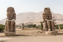 Two stone statues of Pharaoh Amenhotep III at Thebes Necropolis, Luxor, Egypt. The Colossi of Memnon are two massive stone statues of the Pharaoh Amenhotep III royalty free stock photos