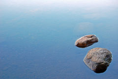 Two stones. Two loneless stones in lake water Stock Photo