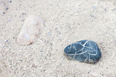 Two stones, light and dark, laying separately on the sand royalty free stock photo