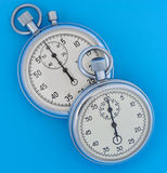 Two stopwatch on blue Royalty Free Stock Photos