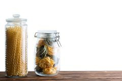 Two storage jars filled with fresh dried pastas. With homemade fettuccine and fusilli bucati lunghi long spirals against a white background with copy space stock photos