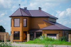 Two storey cottage with garage in a village with beautiful nature. The facade of the house. stock image