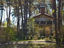 Two-storey country house among a pine forest. There is a small lake in front of the house. Spring vacation in nature. Family vacation outside the city, fresh Royalty Free Stock Images
