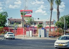 Two-storey firehouse in Rishon LeZion. Rishon LeZion, Israel-June 17, 2017:  2-story red-white building with watching tower is located behind metal fence. It is Royalty Free Stock Images