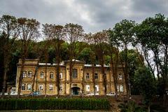 Two-storey oud huis op de achtergrond van bomen en auto's stock foto's