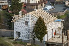 Two-storied cottage under construction. Walls of hollow foam insulation blocksand with window openings,roof beams frame and high. Chimneys, roofing underlayment stock photo