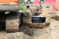 Two storm drains, during repair work on the road in the Leningrad region and tracked excavator. Royalty Free Stock Photos