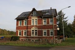 Two-storey brick house with solar panels on the roof royalty free stock images