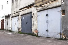Two-story garages for cars. Garage cooperative. Rows of car garages. City architecture. Transport industry. Stone sheds. Rusty iron gate. Brick wall. Perspective stock photos