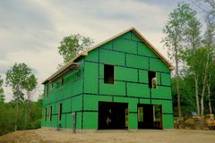 Home Being Built carpentry construction. Two-story home in the process of going up, view from the outside, framework, roof, outer insulation, equipment Stock Photography