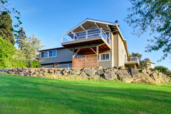 Two story house exterior with gray siding and natural stone landscape design. Stock Images