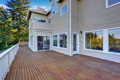 Two story house with wooden walkout deck overlooking backyard garden. royalty free stock photo