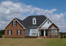 Two Story Residential Home. With brick, stone and board siding on the facade Royalty Free Stock Images