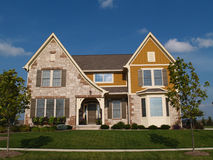 Two story stone, brick and board sided home. Stock Image