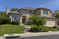 Two Story Traditionally designed Stucco Home. Exterior shot of a nicely landscaped two-story stucco home Stock Images