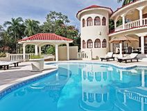 Back patio of tropical villa with large swimming pool royalty free stock photography