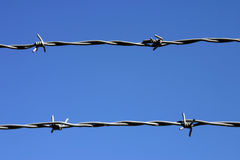 Two strands of barbed wire. Two strands of barbed wire in front of a great blue sky Stock Image