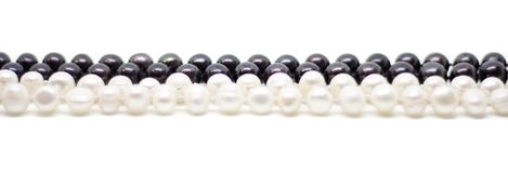 Two strands of white and black pearls intertwined on white background royalty free stock photo