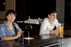 Two strangers drinking at a bar stock photography