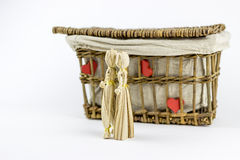 Two straw dolls in front of an old casket. Two straw dolls kissing in front of an old rattan box, on a white background Stock Photo