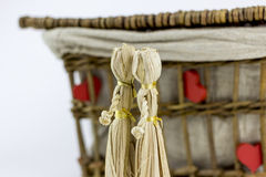 Two straw dolls in front of an old casket. Two straw dolls kissing in front of an old rattan box, on a white background Royalty Free Stock Photography