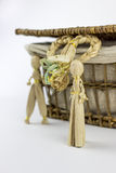 Two straw figurines in front of a vintage box. Two straw figurines in front of a vintage rattan box, on a white background Royalty Free Stock Photography