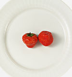 Two strawberries. On white plate on white background Stock Images