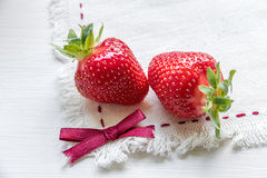 Two strawberries on fabric, ribbon bow. Red, juicy, ripe two strawberries on fabric, ribbon bow Royalty Free Stock Photos
