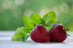 Two strawberries with leaves and mint on wooden table Stock Images