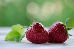 Two strawberries with leaves on wooden table Royalty Free Stock Photography