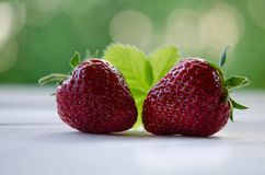 Two strawberries with leaves on wooden table Stock Image
