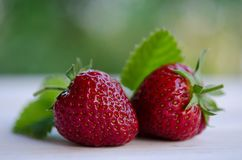 Two strawberries with leaves on wooden table Royalty Free Stock Photos