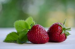 Two strawberries with leaves on wooden table Royalty Free Stock Image